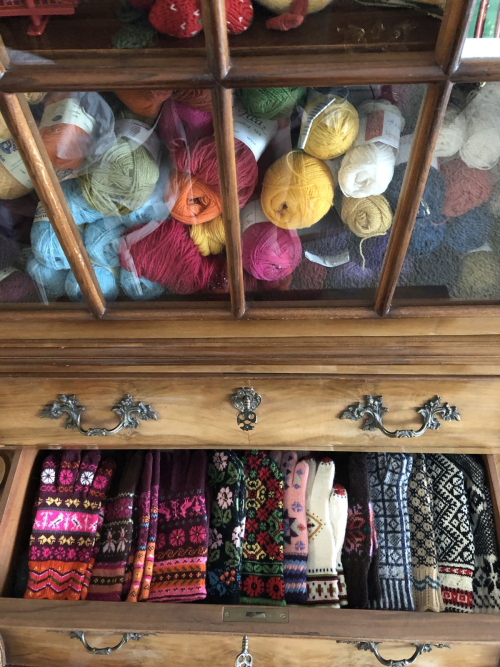 a cabinet full of colorful yarn and some of my knitted mittens and gloves